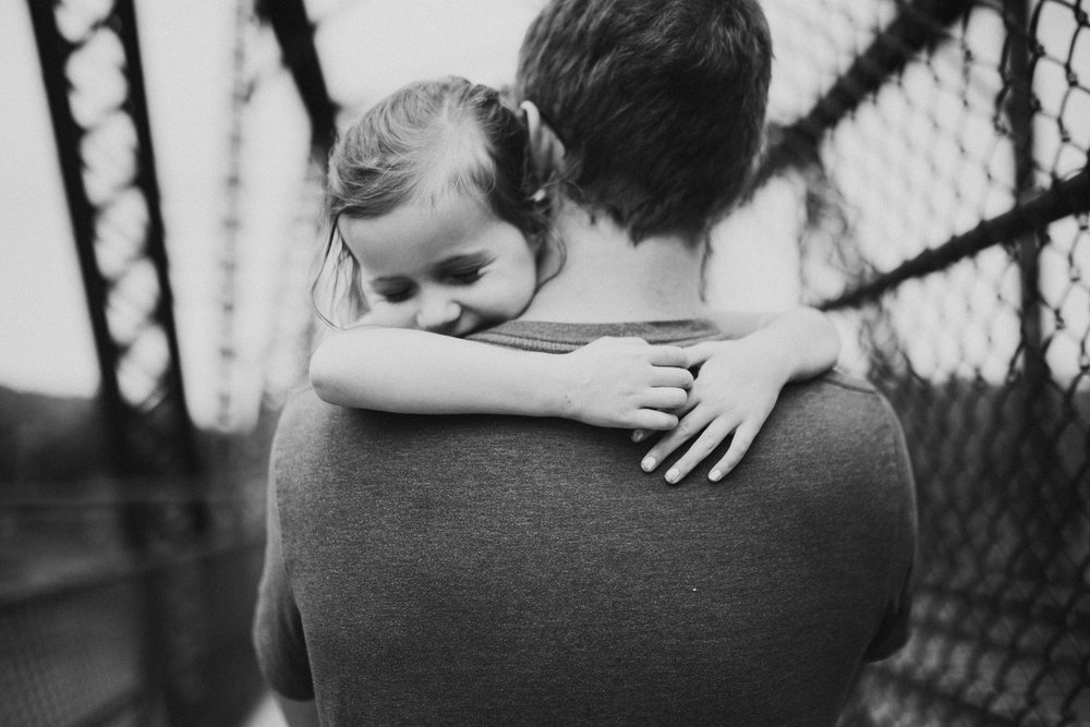 Black and white; dad carrying toddler who wraps her arms around his neck, closes her eyes and smiles in Harpers Ferry, WV