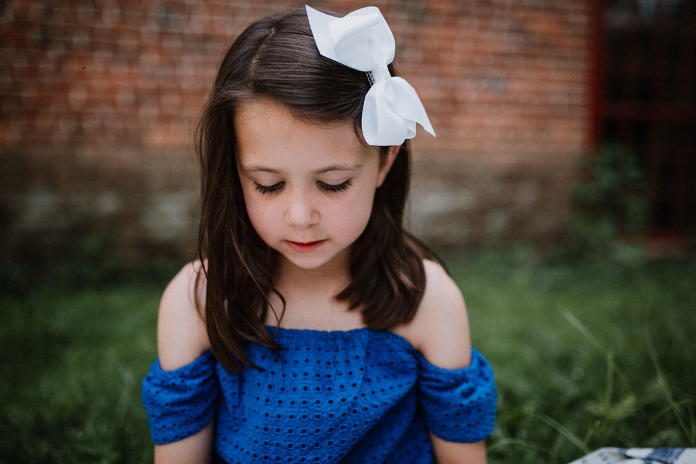 portrait of a young girl in a blue dress and a white bow at Colvin Run Mill in Great Falls