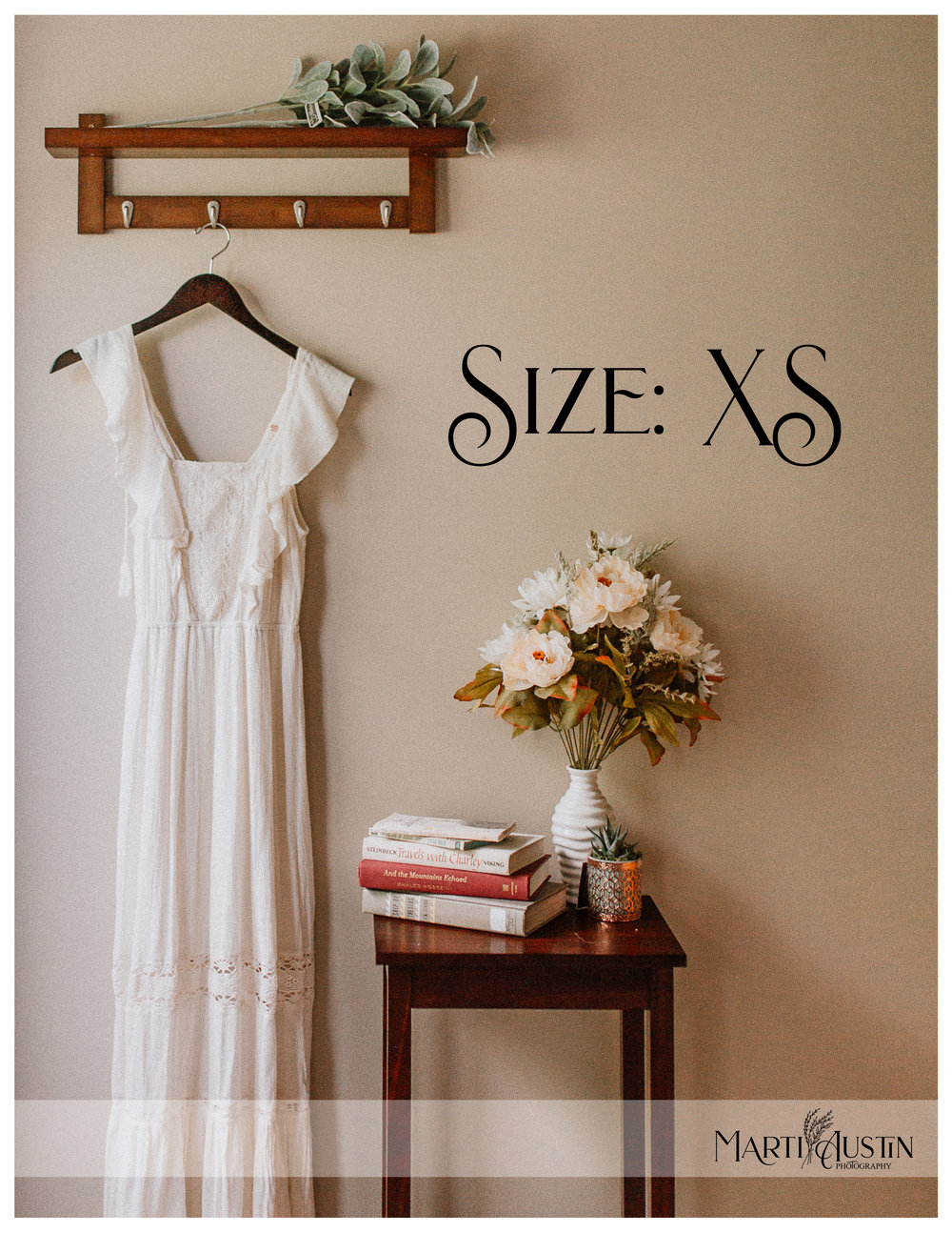 long off-white dress hanging on the wall next to a table with books and flowers