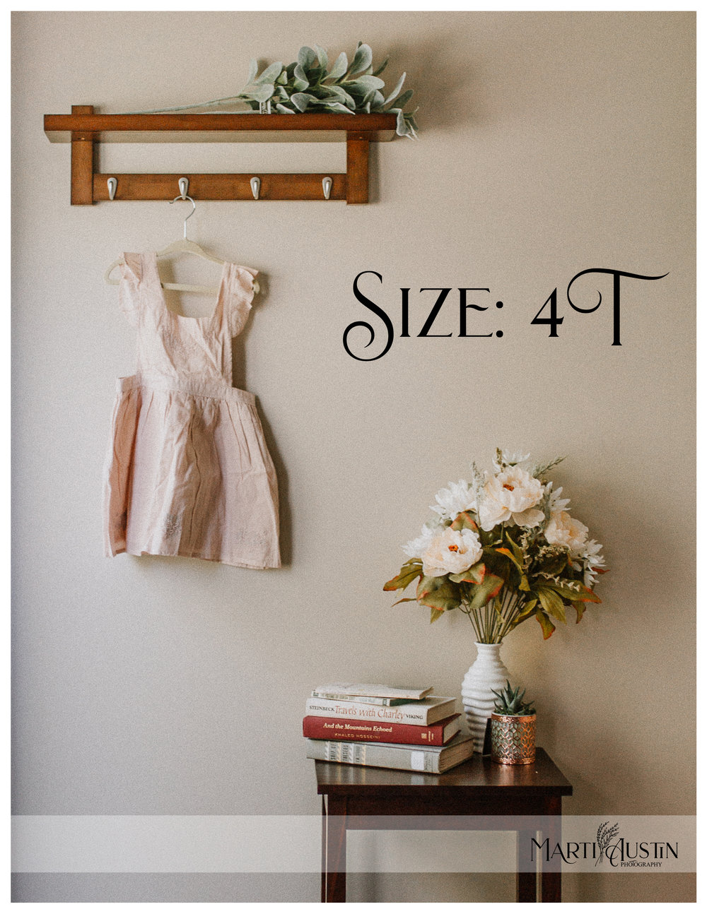 Toddler's pink dress hanging on the wall next to a table with books and flowers