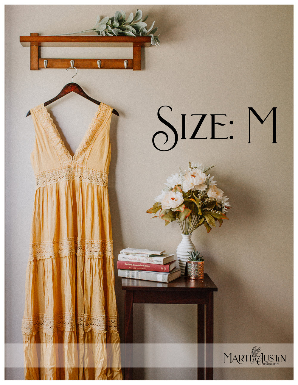 long yellow dress hanging on the wall next to a table with books and flowers