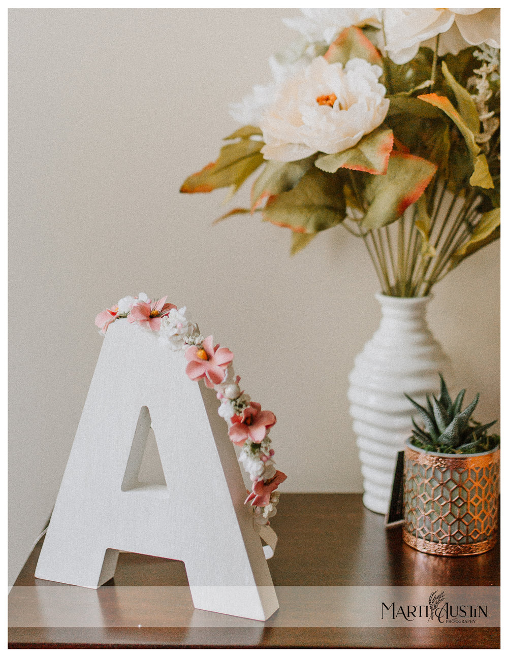 "Pink and white flower crown resting on a wooden letter ""A"" on a table with flowers"