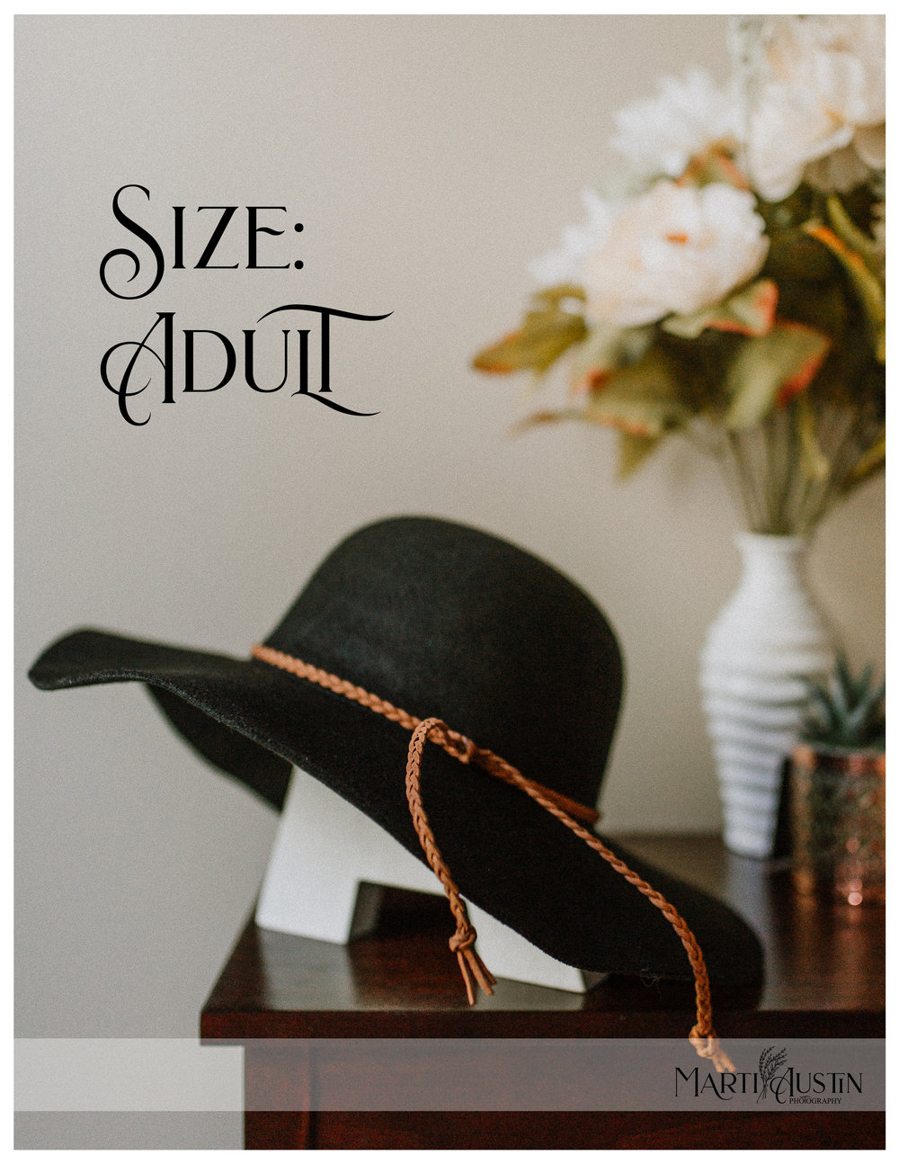 "Black floppy hat resting on a wooden letter ""A"" on a table with flowers"