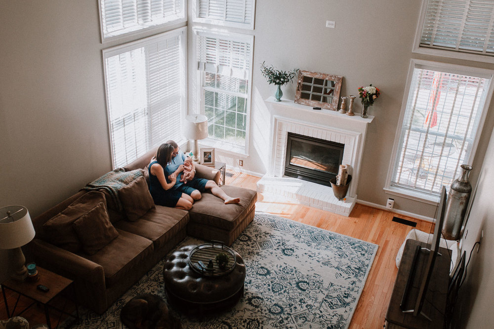Family snuggled together on their couch with their newborn baby boy in Ashburn, Virginia