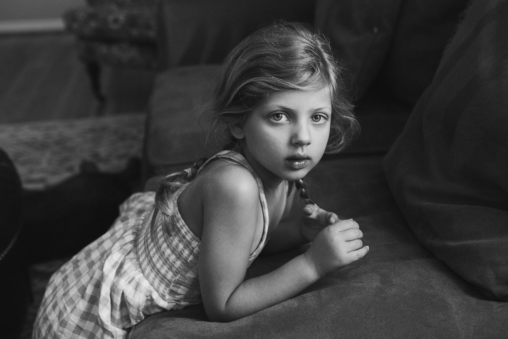 Black and white; portrait of a young girl playing with her hair in Ashburn, Virginia