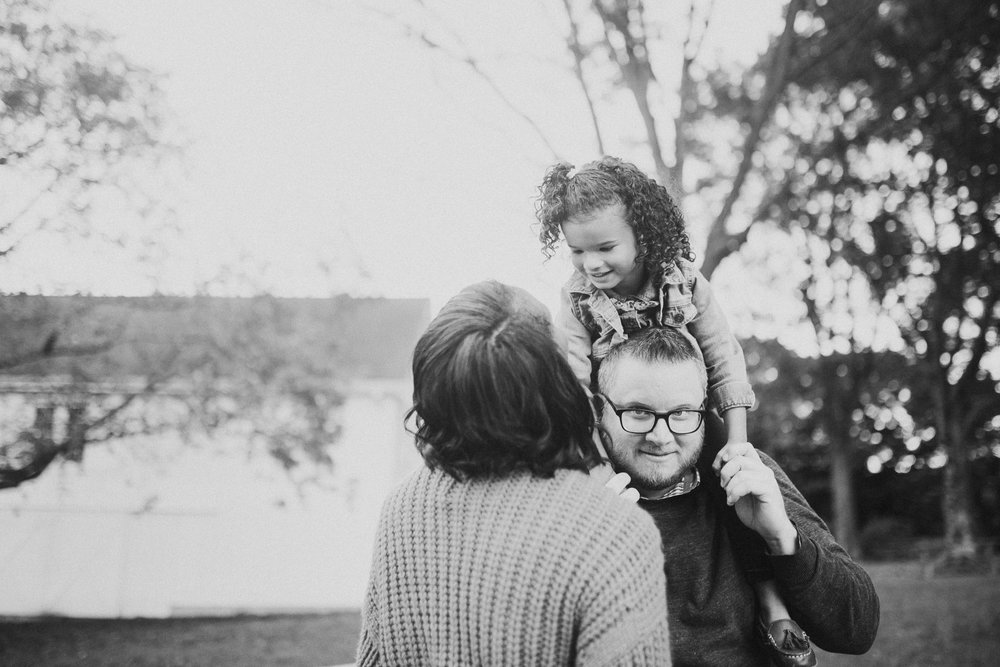 black and white family of three mother father daughter on shoulders sunset golden hour  fall autumn Wolf Trap Vienna Virginia Lifestyle Documentary Family Marti Austin Photography