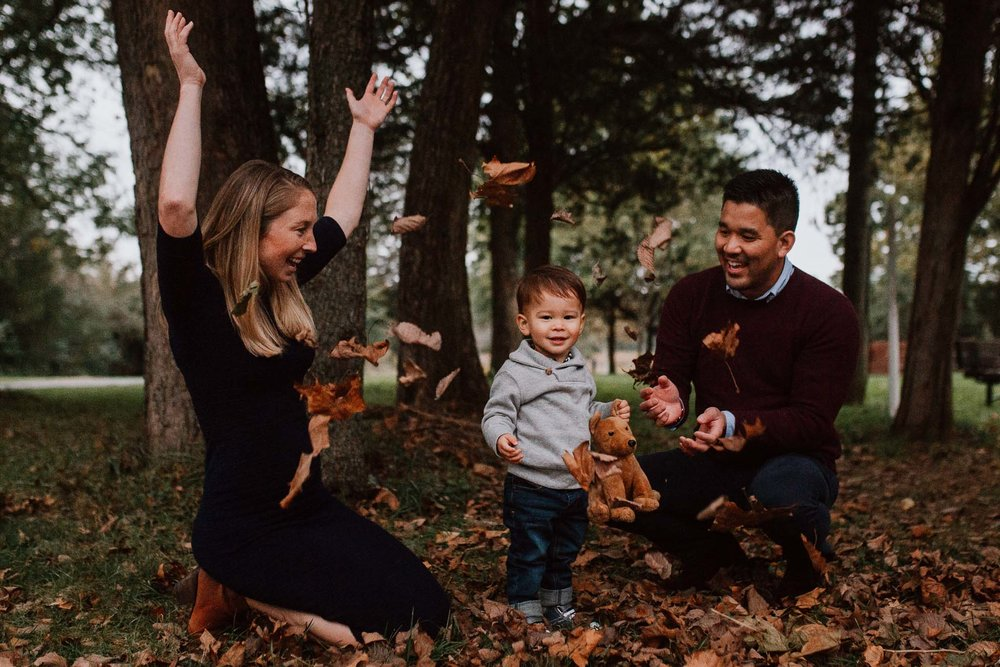 mother father son toddler throw leaves fall autumn family lifestyle documentary Claude Moore Park Sterling Virginia Marti Austin Photography