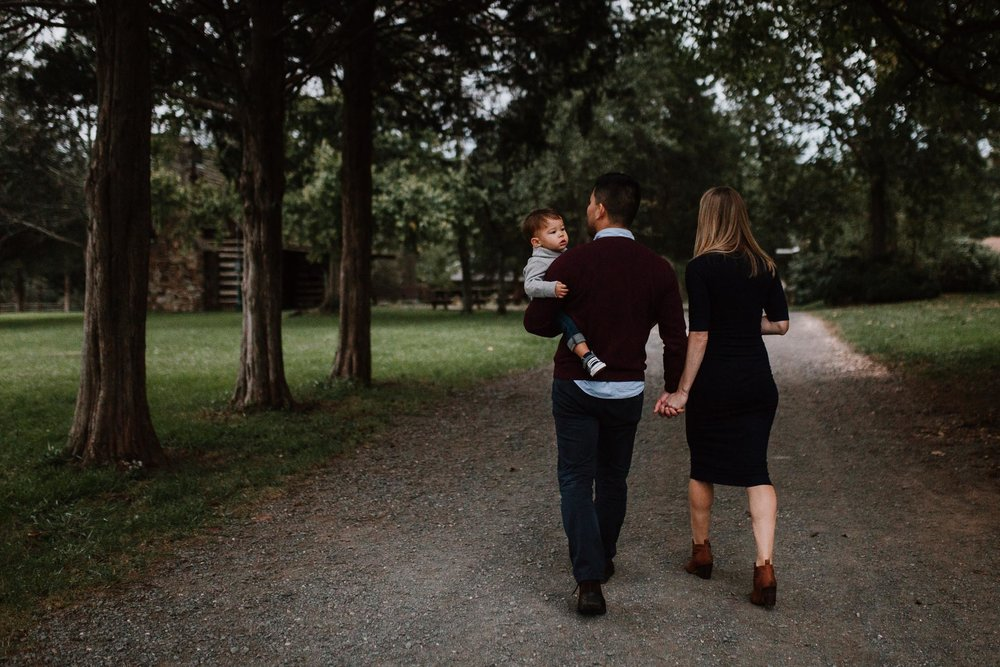 family of three walk tree lined path holding hands fall autumn family lifestyle documentary Claude Moore Park Sterling Virginia Marti Austin Photography