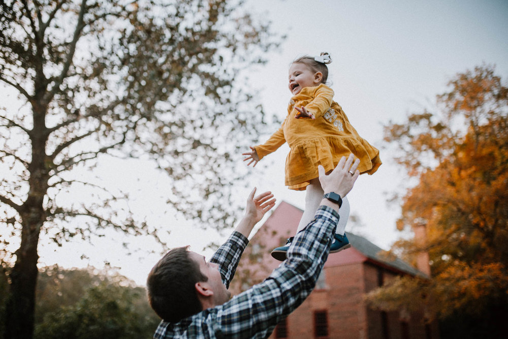 father throwing daughter in air fall sunset family lifestyle documentary Colvin Run Mill Great Falls Virginia Marti Austin Photography