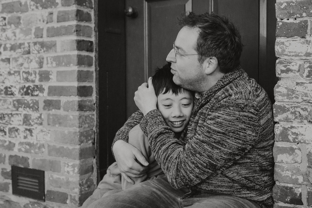 black and white father son hug Lifestyle Documentary Found Families Adoption Outdoor Golden Hour Sunset Colvin Run Mill Great Falls Virginia Marti Austin Photography