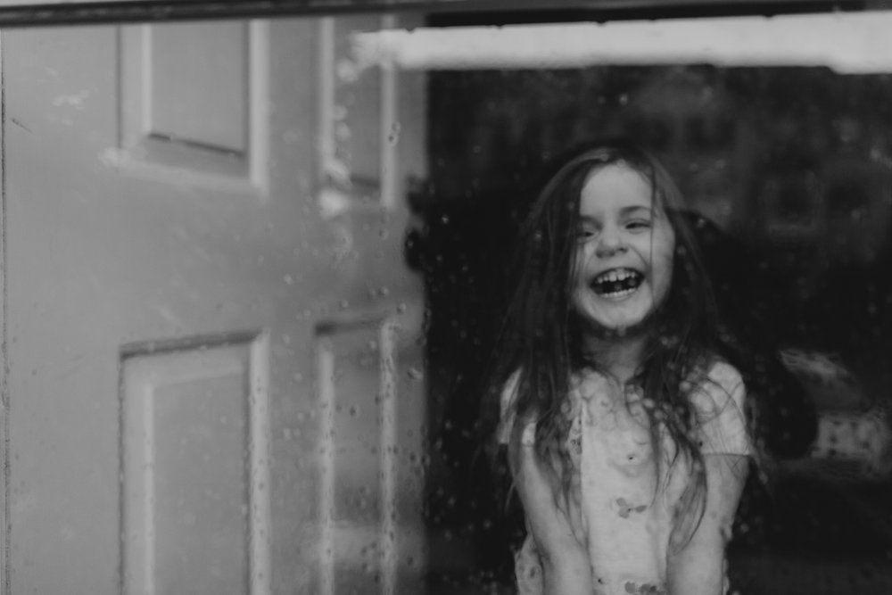 black and white girl laughing behind glass door lifestyle documentary family Ashburn Loudoun northern Virginia  childhood Marti Austin Photography