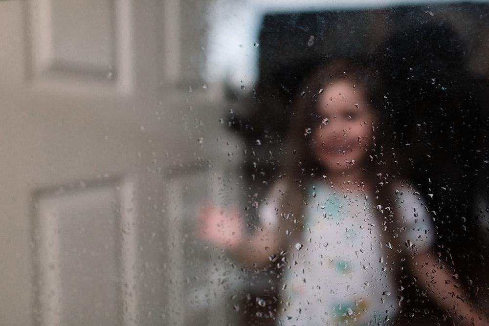 girl behind rainy glass door lifestyle documentary family Ashburn Loudoun northern Virginia  childhood Marti Austin Photography