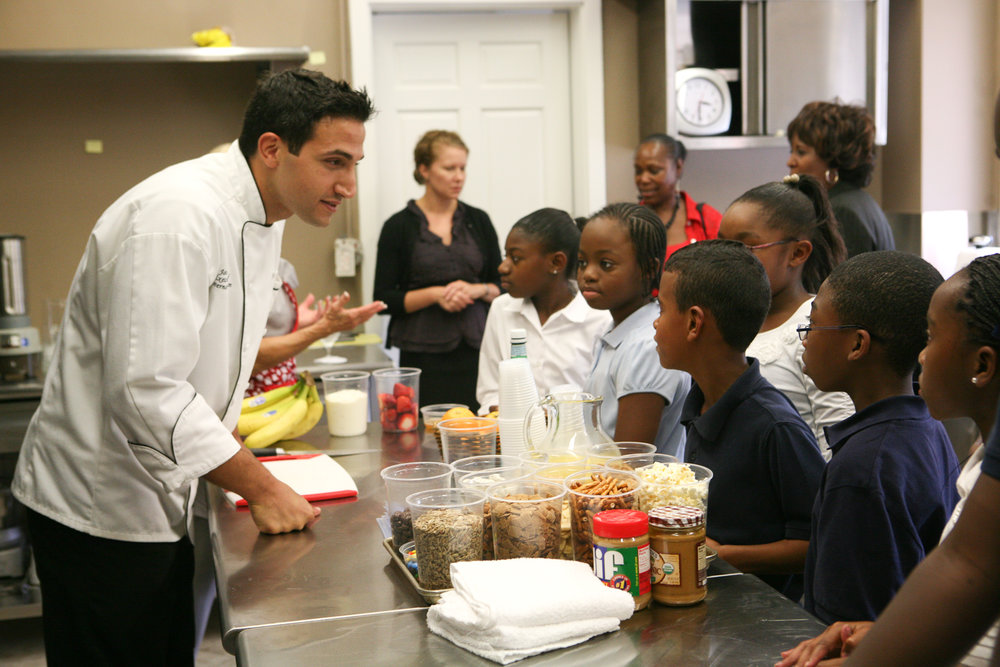 Chef Minas, at the Governor's Mansion,educating local students and community members demonstrating a simple healthy snack substitute.
