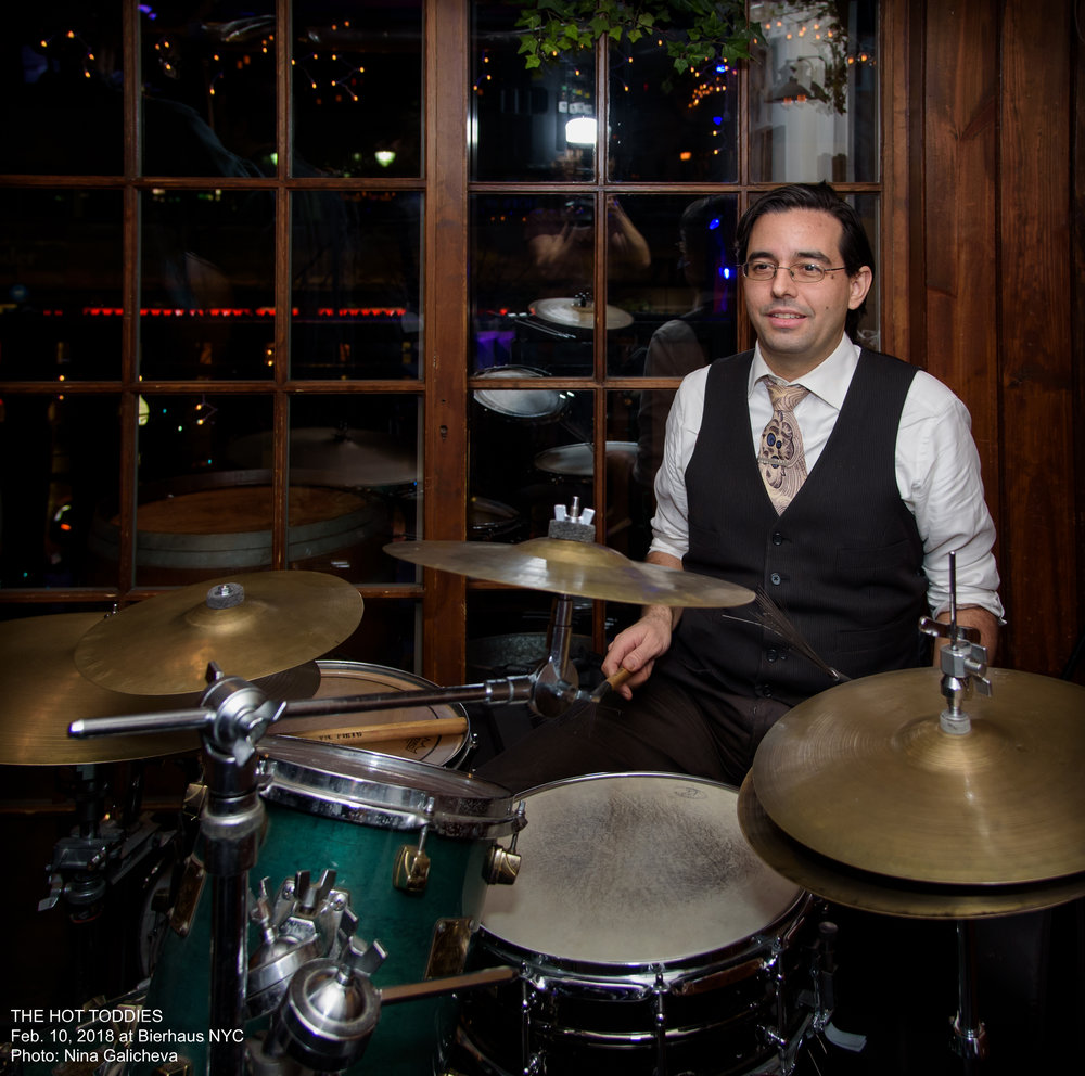 Patrick Soluri - Patrick is a drummer, composer, and producer from New York City. He began percussion at age 5, drums at age of 7, playing in jazz and alt rock bands in high school. At Bennington College, he studied jazz with Bill Dixon, as well as Western and African drumming with Milford Graves.Discovering a passion for composing for orchestra, ballet, and opera, he transferred to Manhattan School of Music receiving a BM in Classical Composing, followed by a MM as recipient of the Bomhard Fellowship in Opera Composition at the University of Louisville. Since graduation he's had 8 commissioned ballet scores performed around the world including premiere's at Staatsballet Berlin, Ballet de l'Opéra National de Bordeaux, and The Kennedy Center in DC (conducting his own world premiere). Performances of his operatic work include four premieres at Carnegie Hall, a full production at Fort Worth Opera, winner of the 2013 Frontiers Competion, and finalist in 2018 Pellicciotti Opera Prize. More info on his composing career at www.PatrickSoluri.comIn 2000 Patrick became an avid swing dancer, and soon after started Prohibition Productions, which currently is the largest independent producer of hot jazz and swing dance events in New York City... more info at www.ProhibitionProductions.comAfter years away, Patrick is thrilled to be playing drums again, and performing with the Hot Toddies!