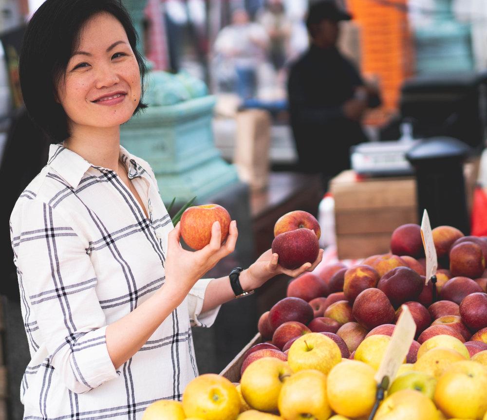 Cat-FarmersMarket-holding-apples-smiling.jpg