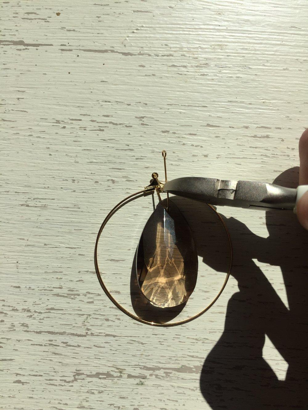 Thread through opening at top of hoop. Bend over towards gem to create loop. -