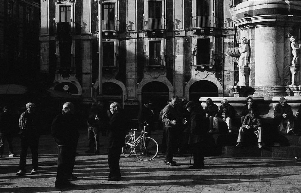 Hard talks in the square. Maybe things, we shouldn't know about. Outside of the box #9 Images from my archive. #Sicily #Sicilia #Italy #Italia #neorealism #square #people #film #filmisnotdead #fishes #fish #sicilians #photooftheday #antoniosansica #streetphotography #35mm #urban #kodak #myfeatureshoot #italians #kodaktrix400 #bw #blackandwhite #catania