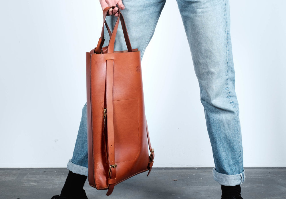 The Totebackpack is a multifunctional unisex leatherbag that can be used either as a backpack, totebag or a handbag by pulling the straps on another position. When worn it will close itself automatically by the straps running through the top of the bag. It features an 23 x 15 cm outside pocket with a zipp-closure and a key holder on the inside of the bag.The straps are made of strong 3.5 mm thick leather that is connected with hand forged solid brass rivets.The cut edges of the leather are carefully rounded off and hand polished with beeswax to smooth finish.