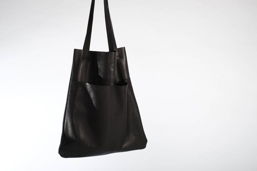 The Totebag S is made of  1.5 mm thin and very soft tumbled leather. It is a simple top open tote bag that features two additional outside pockets on the front and one big inside pocket  with a zip closure accessible from the back. The straps are double layer and made of the same supple leather.