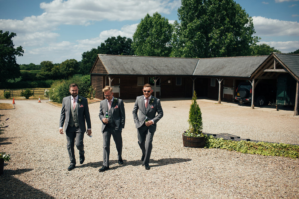 Groomsmen walking through courtyard
