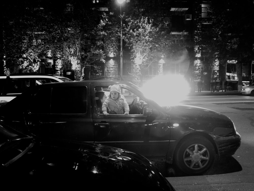 a child looks out from a protesting car as another car behind it flashes a strobe light.