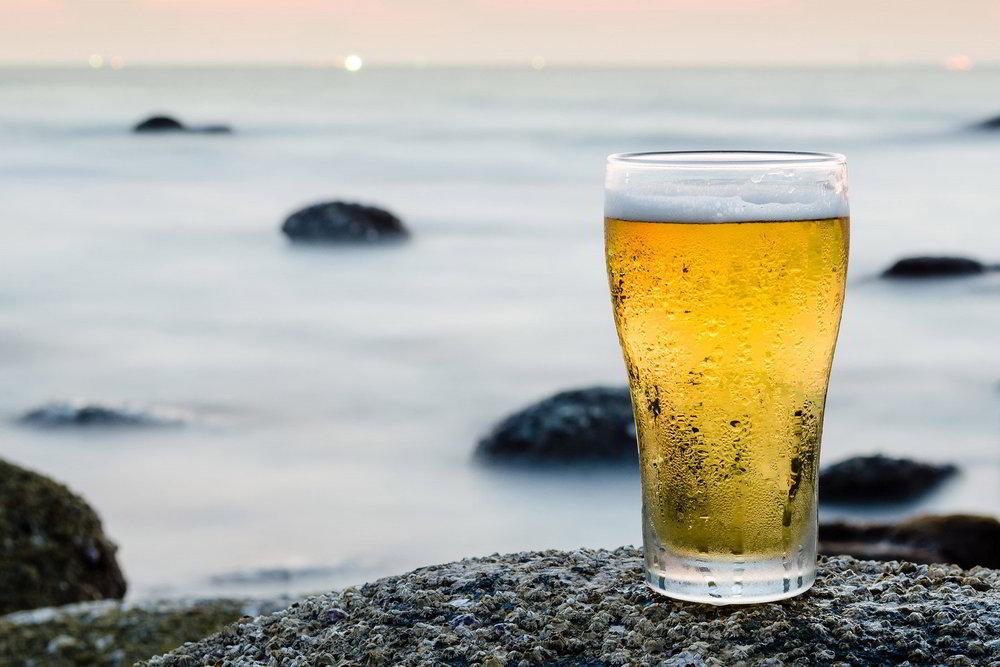 glass-of-beer-against-sea-and-coastline.jpg