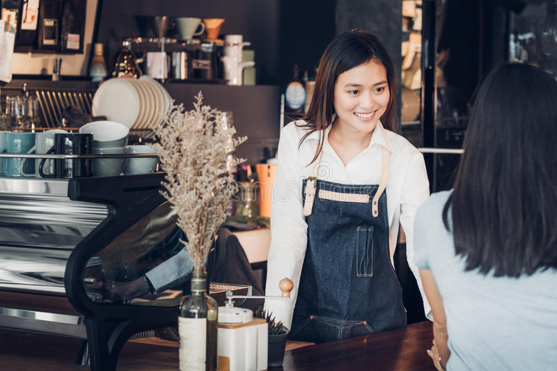 asian-woman-barista-wear-jean-apron-holding-coffee-cup-served-to-women-customer-bar-counter-smile-emotion-cafe-restaurant-98995455.jpg