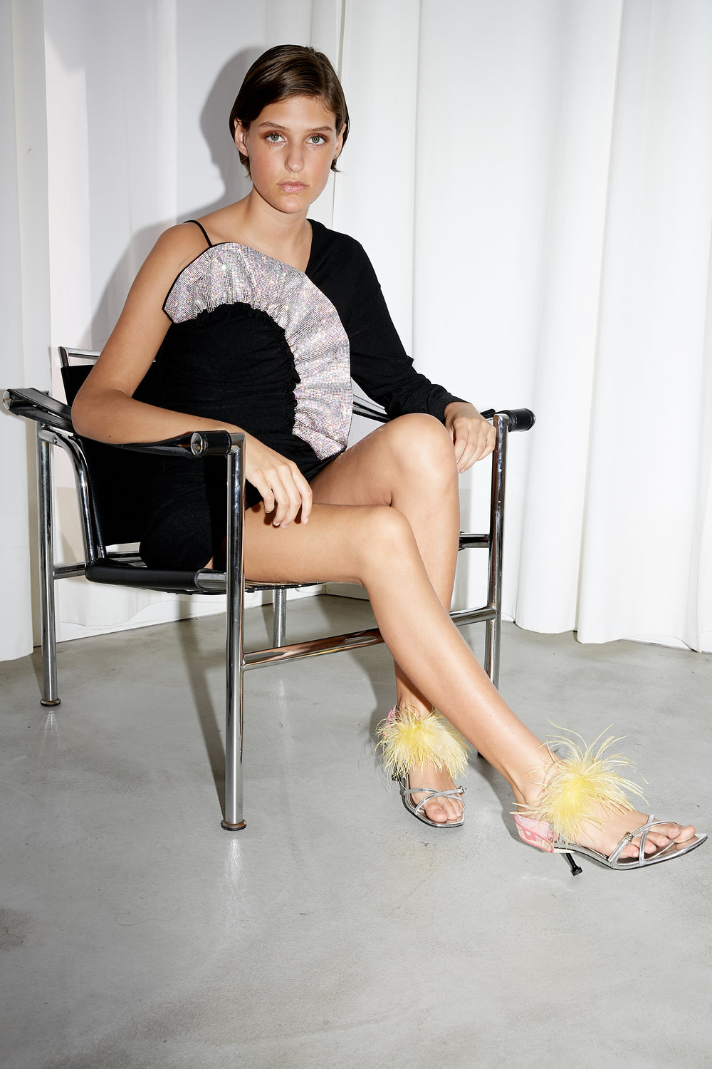 Model sits in chair extending on leg in one sleeve black dress with crystal ruffle neckline