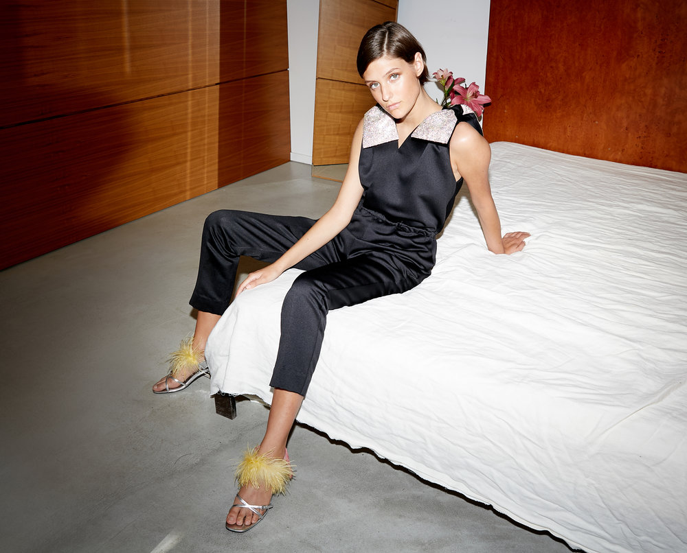 Model sits on bed in sleeveless black satin v neck jumpsuit with crystal bows at it's shoulders