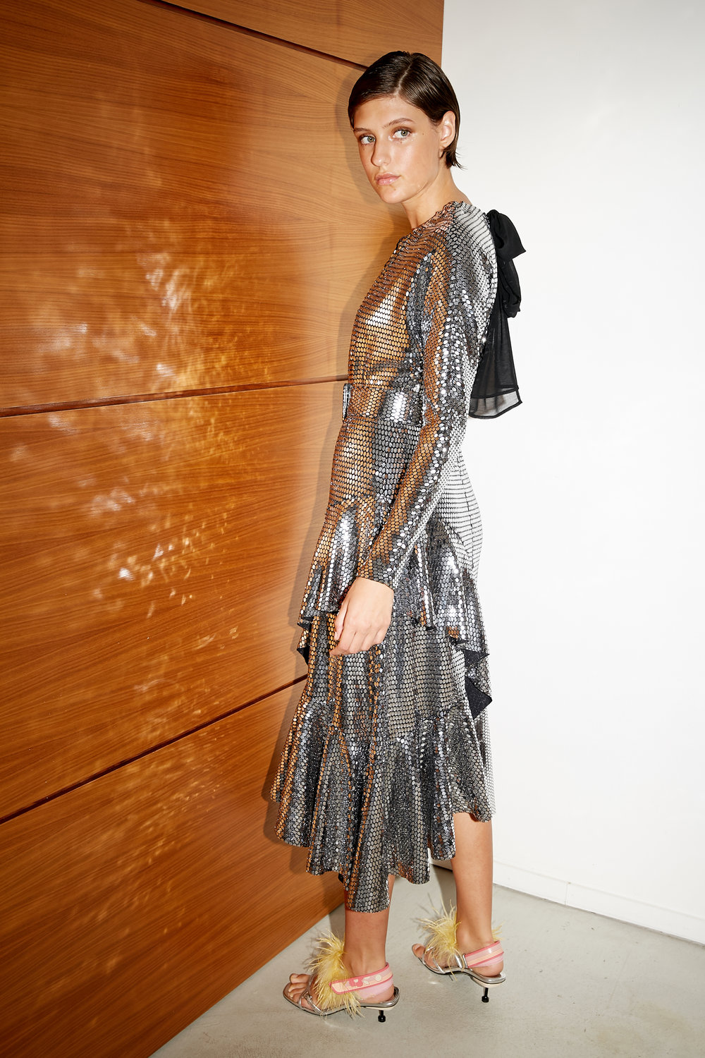Model shows backside of reflective mirrored jersey dress with long sleeves and ruffled hem