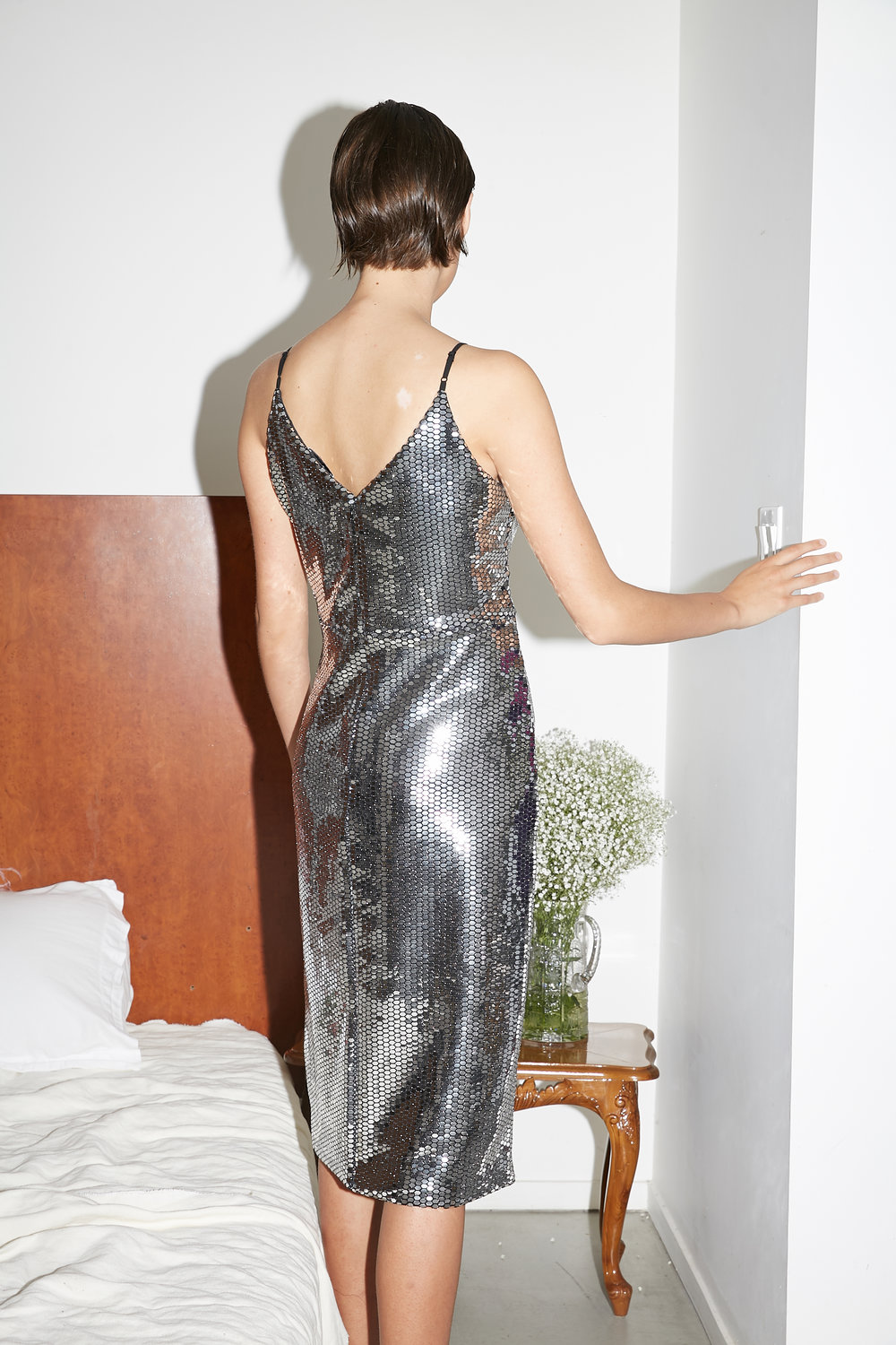 Model shows backside of knot front knee length mirrored wrap dress