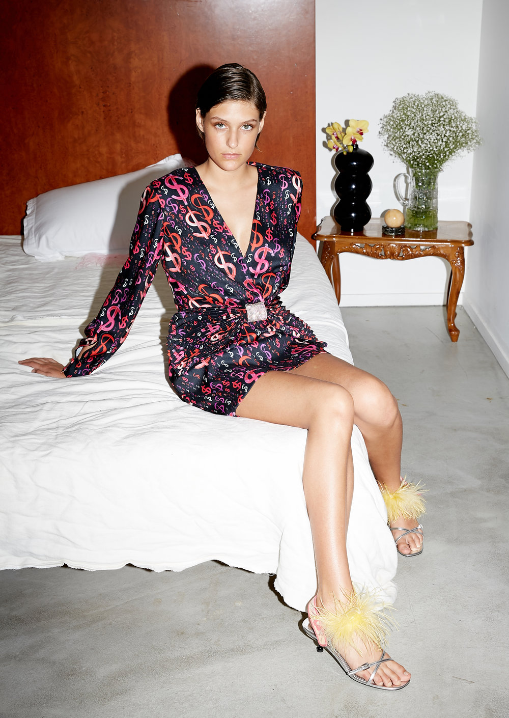 Model sits on bed in short black long sleeve dress, black with rad and pink dollar signs all over dress and pleated bow with crystal center at waist