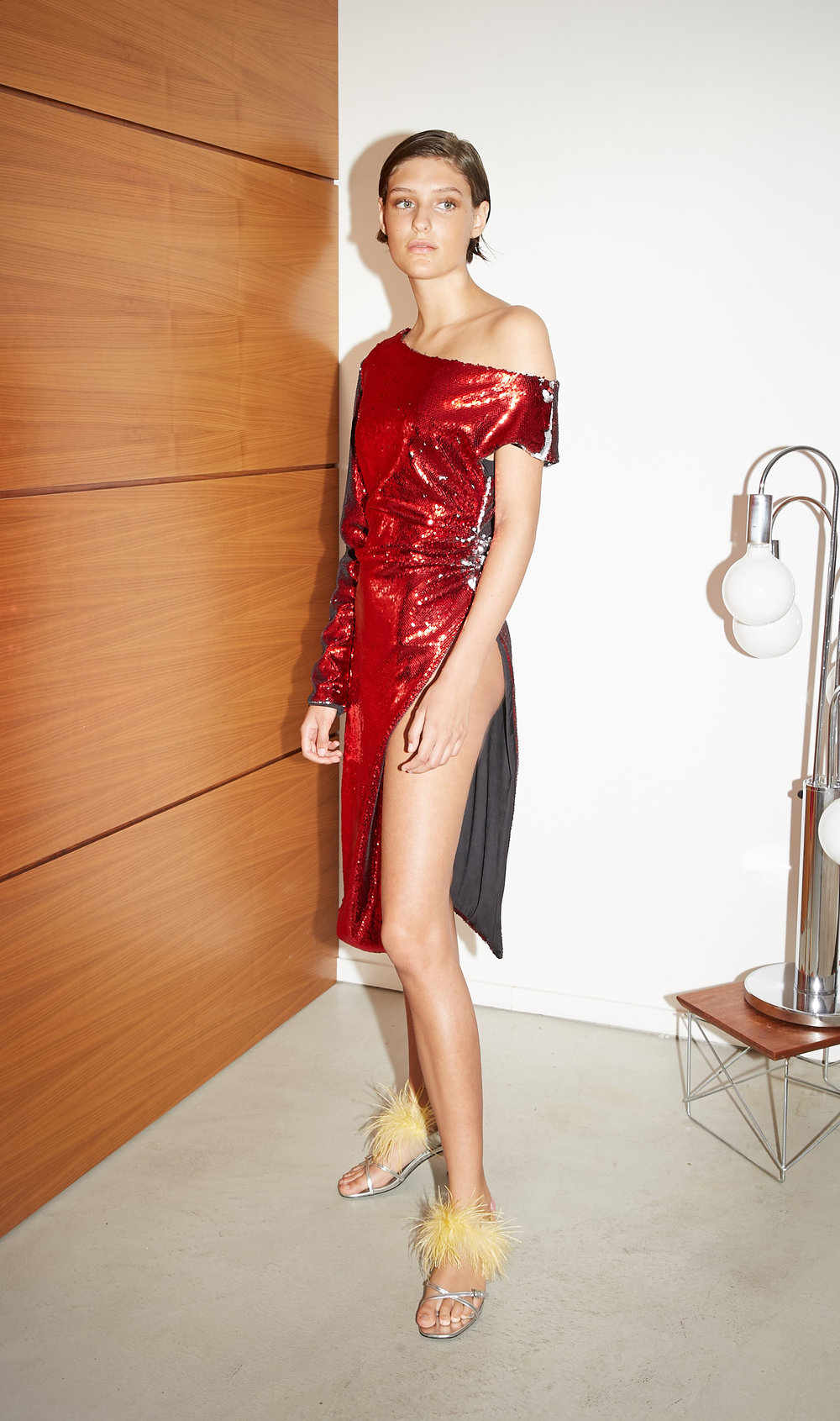 Model stands in red sequin one sleeve dress