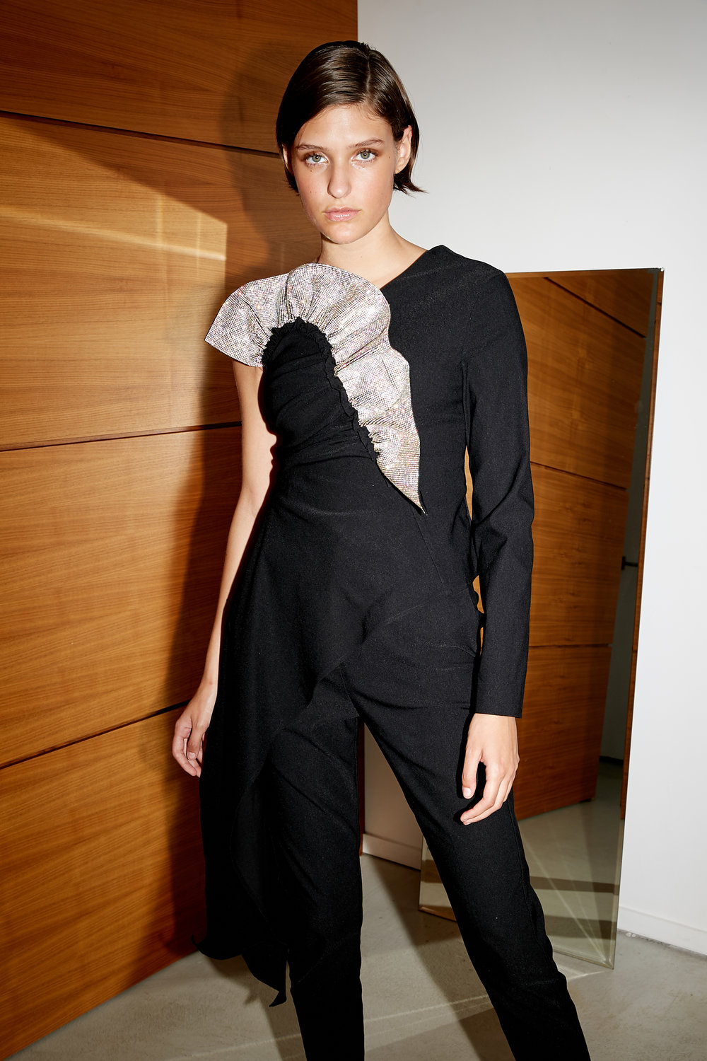Model stands in matte black one shoulder top with ruffle crystal detail and tailored black pants