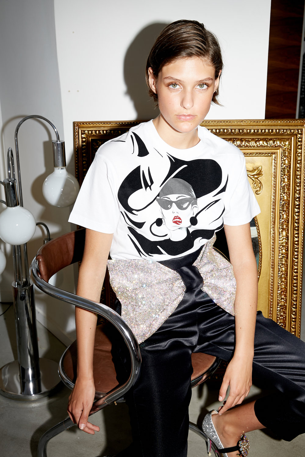 Model sits in whit t-shirt with woman's face graphic and black satin trousers with oversized crystal bow at waist