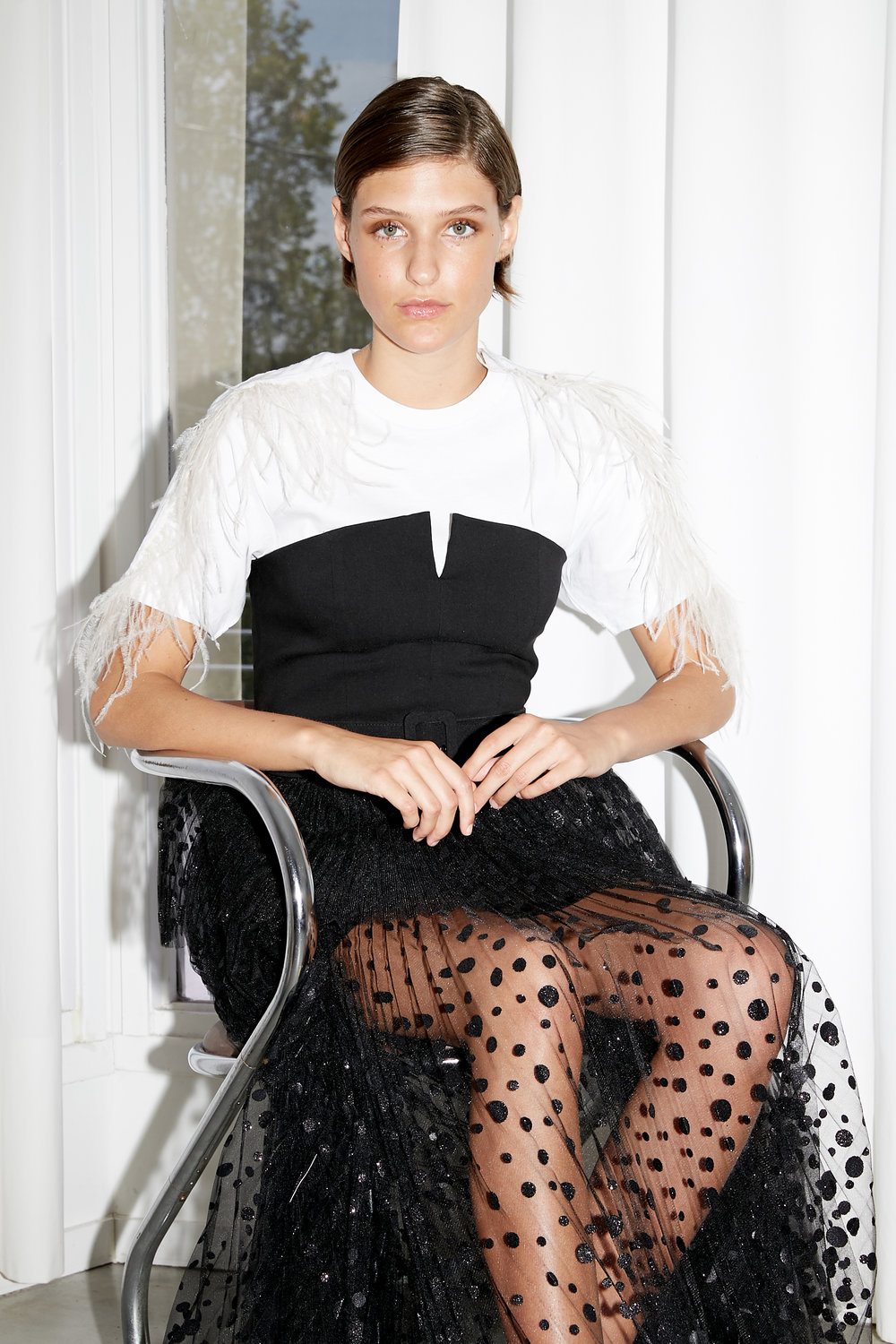 Model is seated in white t-shirt with feather trim and black bustier top and pleated sparkling chiffon skirt