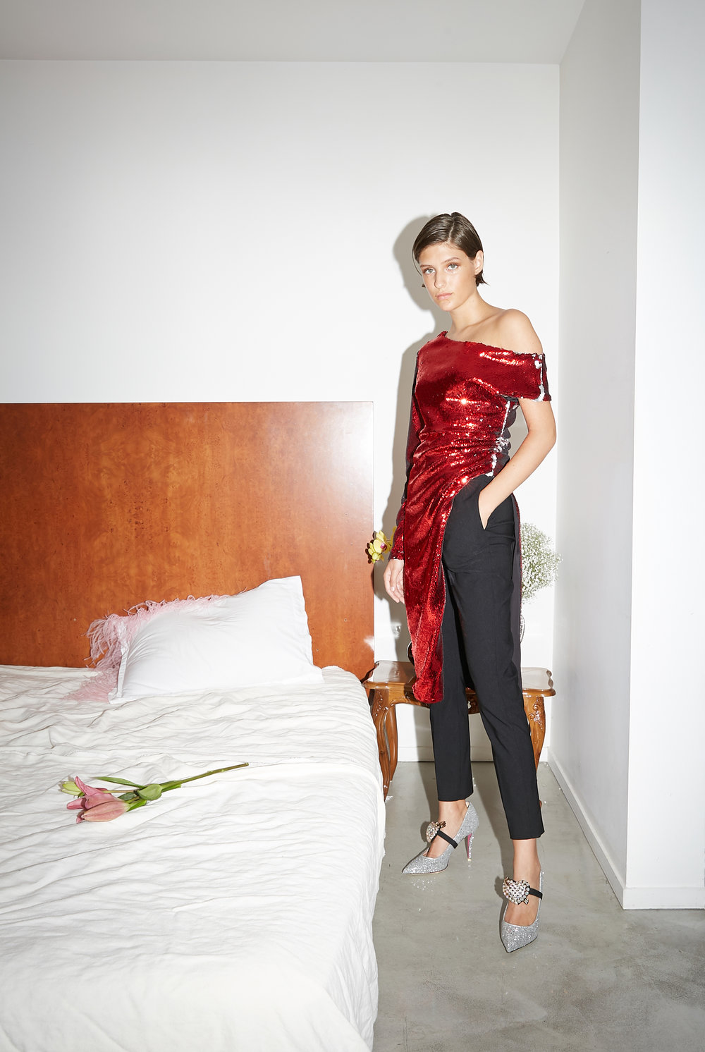 Model stands in red sequin one sleeve dress over tailored black pants