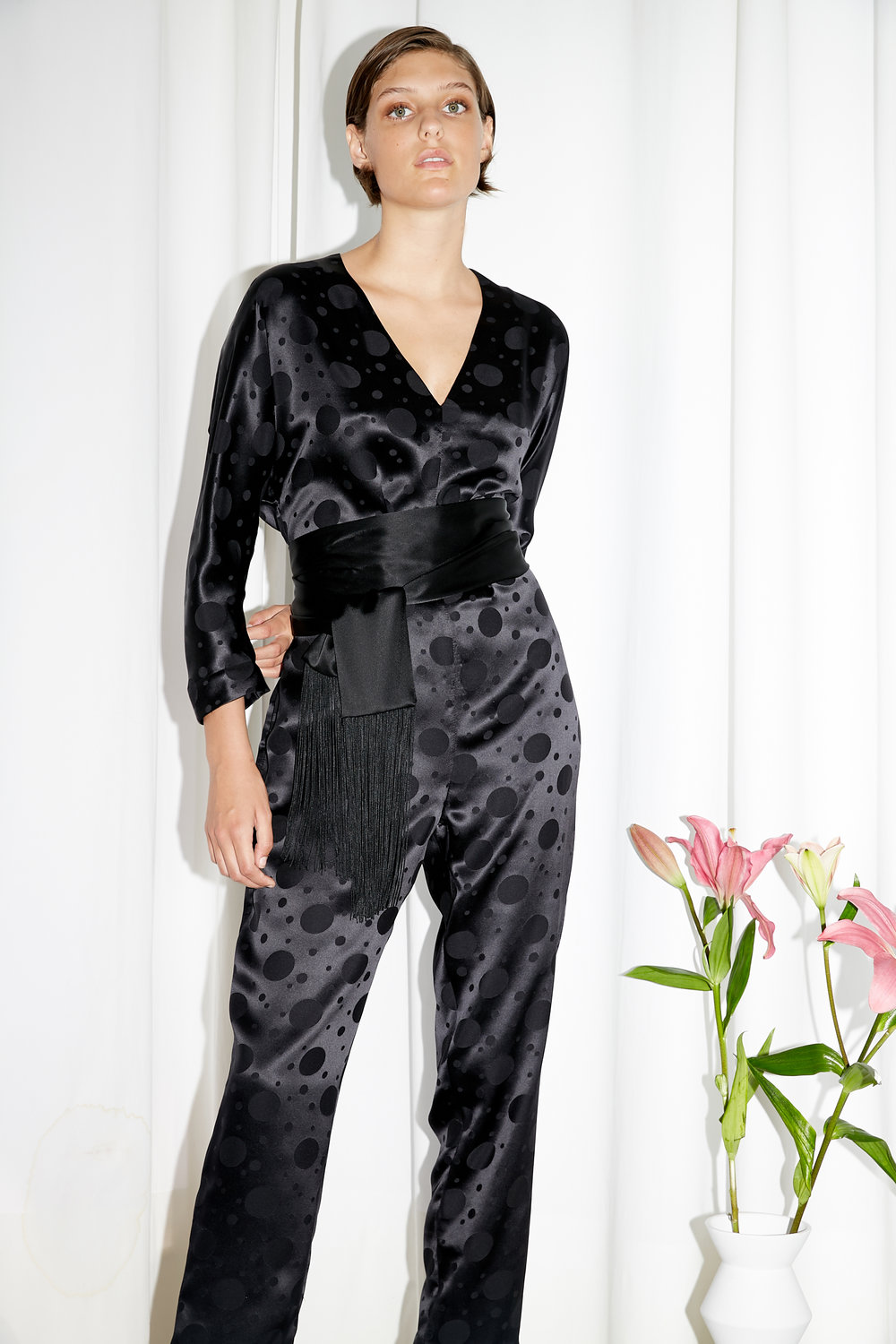 Model stands in satin V neck long sleeve top with matte polka dots and matching pants