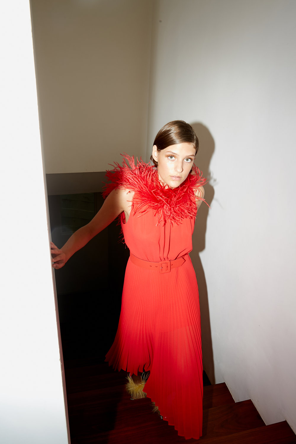 Model ascends staircase in red sleeveless dress with weather trim along neckline