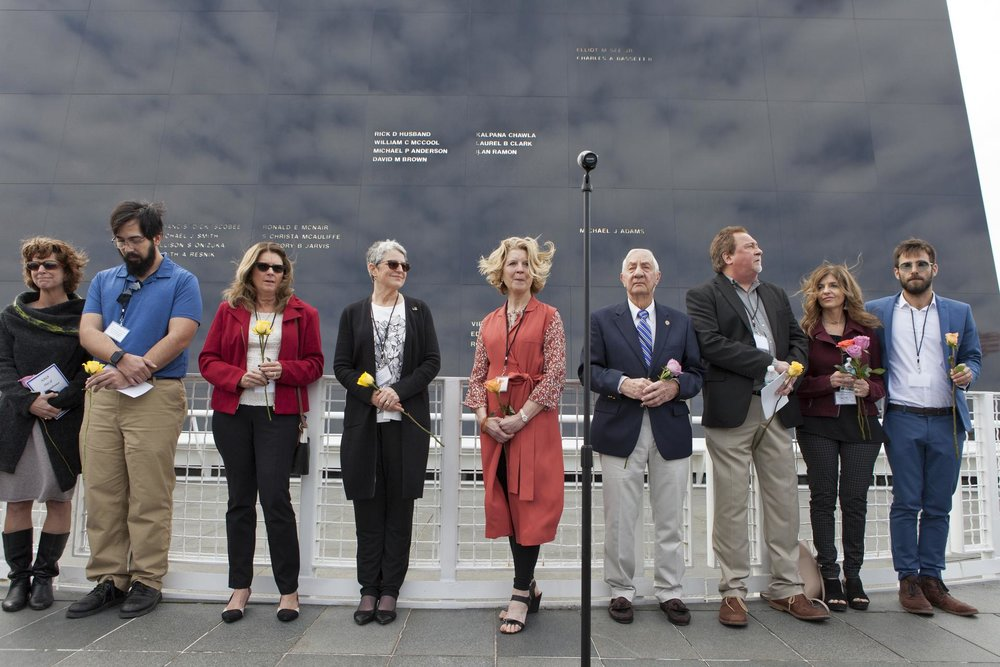 The family members of the fallen astronauts stand in front of the Space Mirror Memorial.