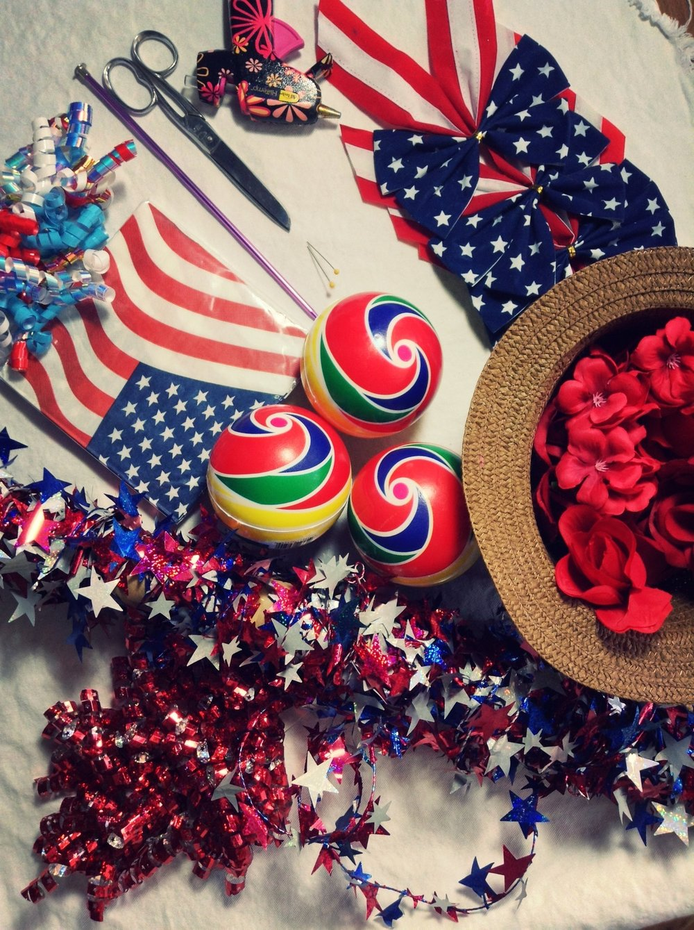 Supplies - -Round foam/styrofoam balls- Toy athetic foam balls from Dollar Tree-Flag themes paper napkins/tissue paper-Artificial flowers-Red, white & blue star wired garland-Flag themed bows-Yarn-Curled gift wrap ribbon/scissor curled ribbon-Hot glue gun/hot glue sticks-Scissors-Wire cutter/jewelry scissors-Strait pin/needle-Knitting needle/chop stick/long narrow stick with pointy end-Scotch tape-Twist ties (optional)