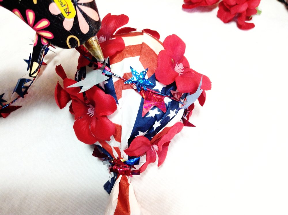 Create a swirl affect by wrapping the garland around the ball and securing with hot glue. Doing it this way is a little trickier, but with a little more time & patience you could totally do it!
