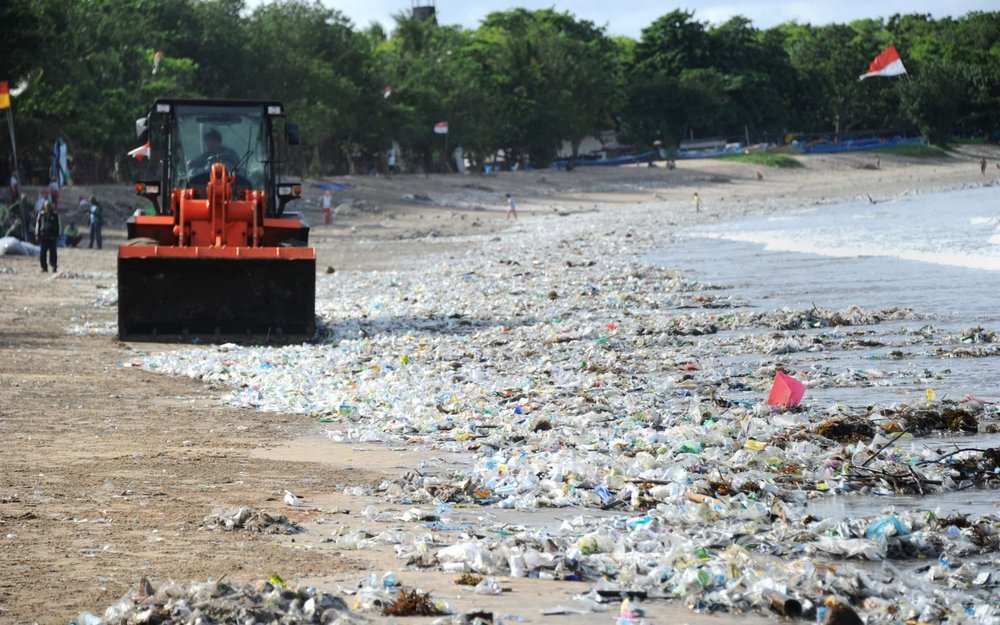 Trash collector cleaning trash on Kuta beach. Image via the Telegraph