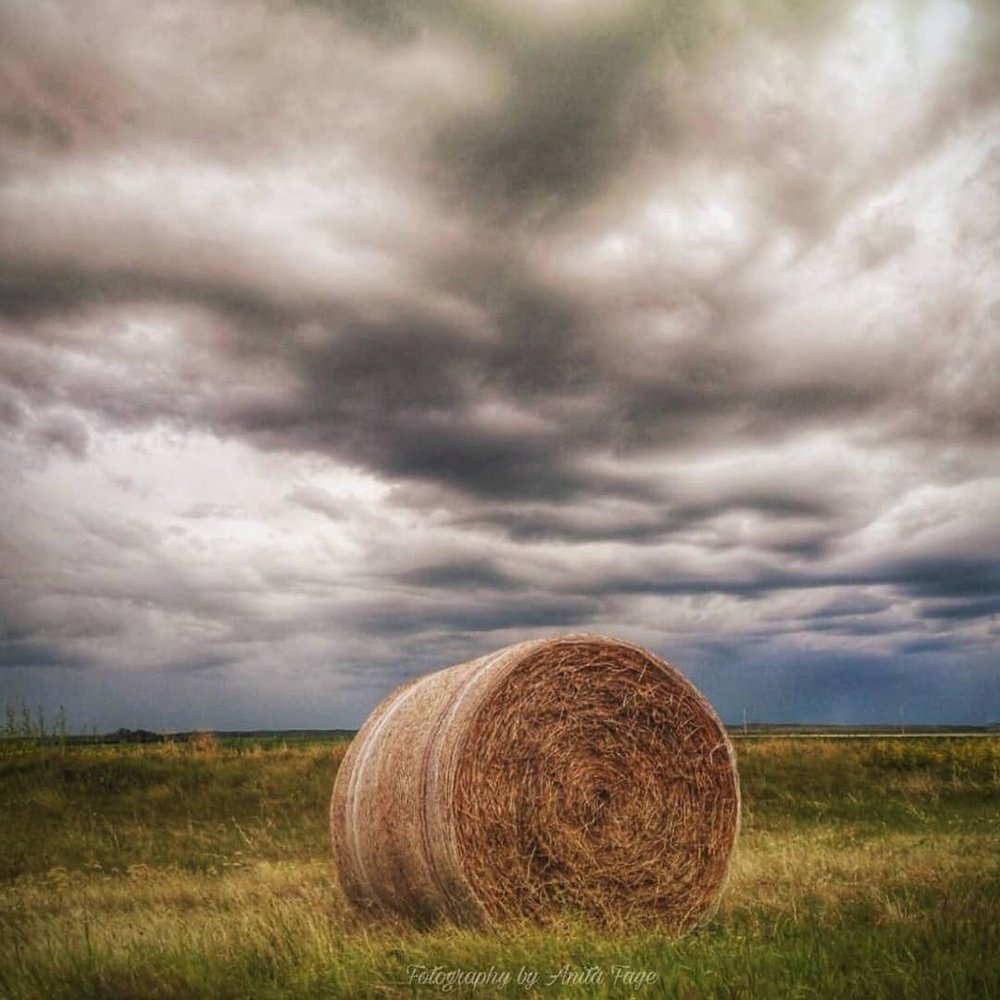 Herbert, SK - The Story: Two common sights across Saskatchewan are in this photo ... storm clouds and a hay bale. Each are a symbol of this province that bills itself as the