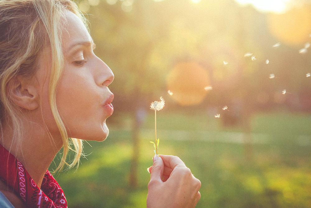 Close-up-of-a-happy-young-blonde-woman-blowing-dandelion-543837766_2125x1416.jpeg