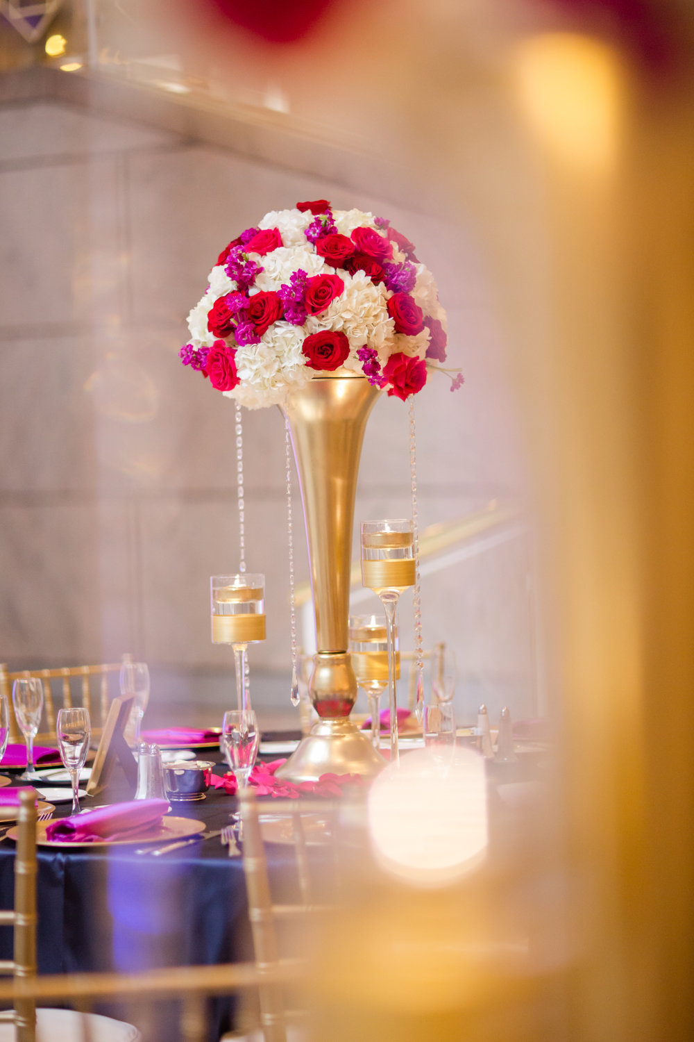 Picture by Naomi Sheress:Tall Arrangements with gold vases and floating candles.