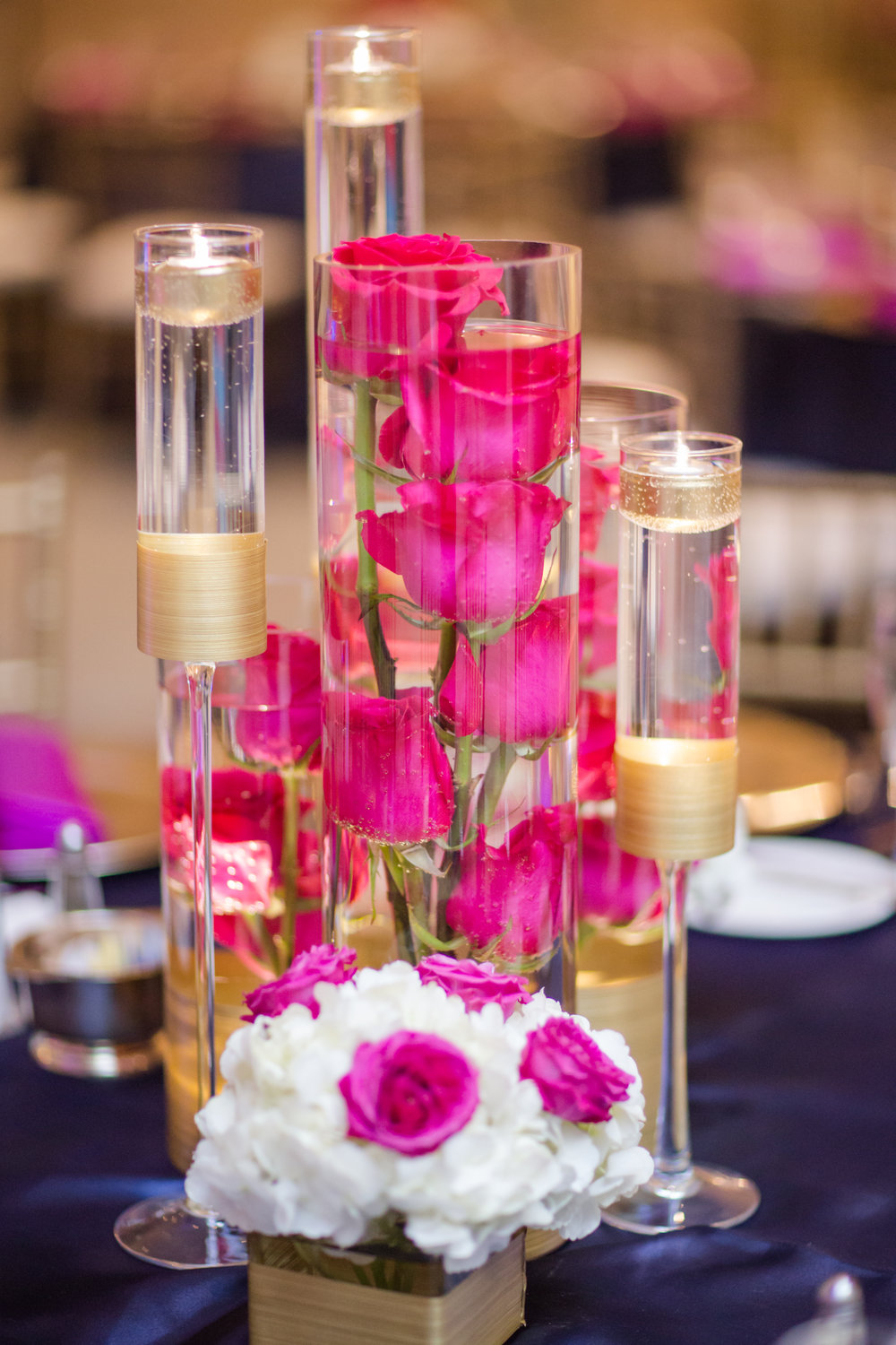 Picture by Naomi Sheress:Medium centerpieces with floating pink roses and candles.