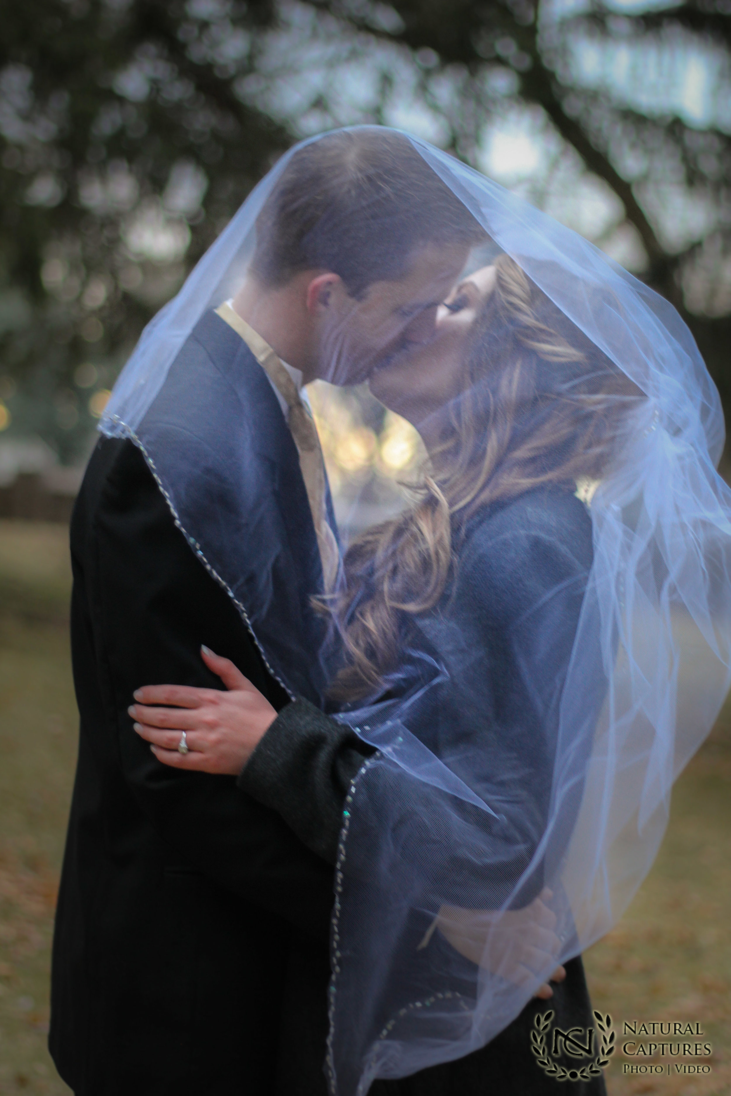 Bride & Groom under Veil kissing