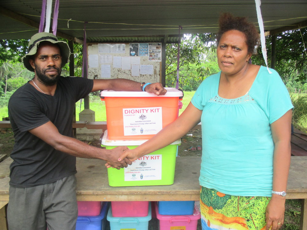 Photo caption: Florian, a 45-year old mother of seven from the village of Navuti, in West Ambae receiving a dignity kit from ADRA volunteer Stanley David. Photo credit: Caritas/ADRA. Date: January 2018.