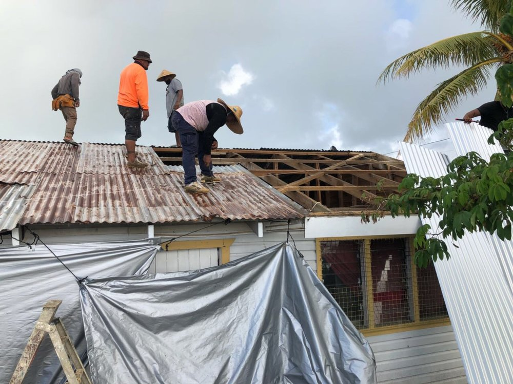 Photo caption: The field team taking off the tarpaulin and starting on the reconstruction. Photo credit: CARE Australia. Date: May 2018.